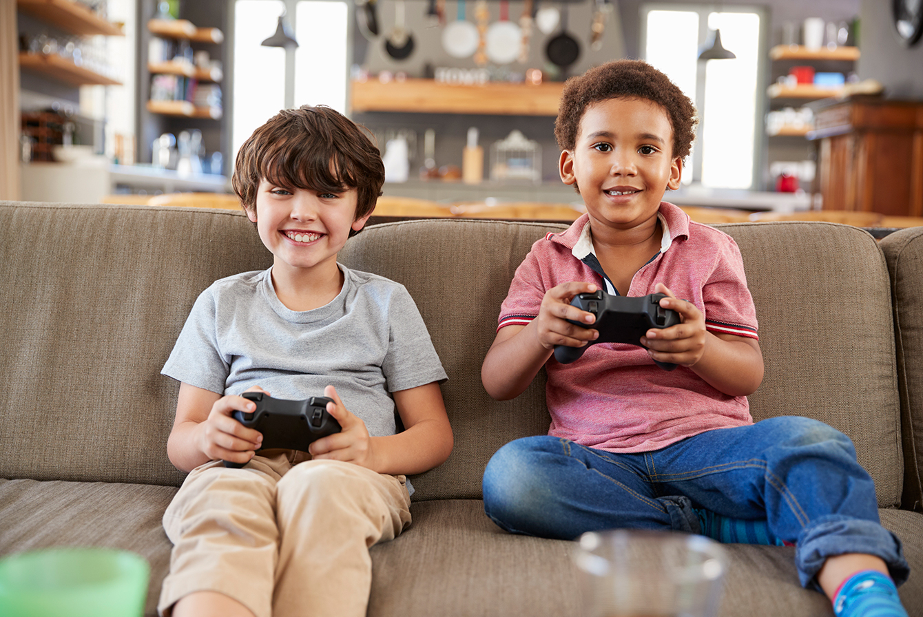 Boys sitting on couch playing video games