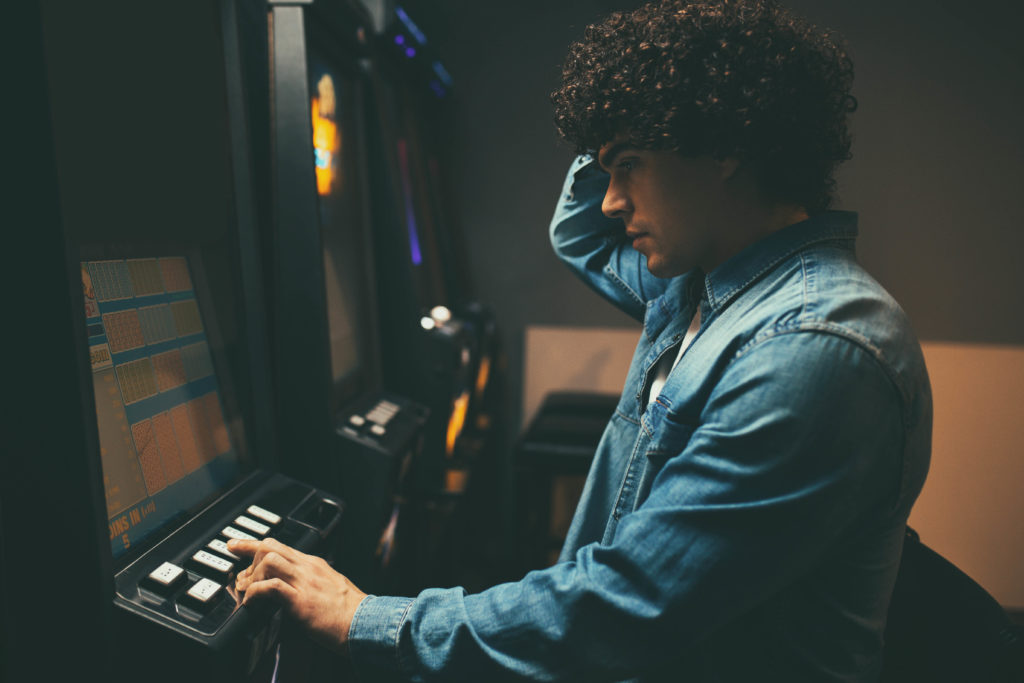 Young man worried at slot machine